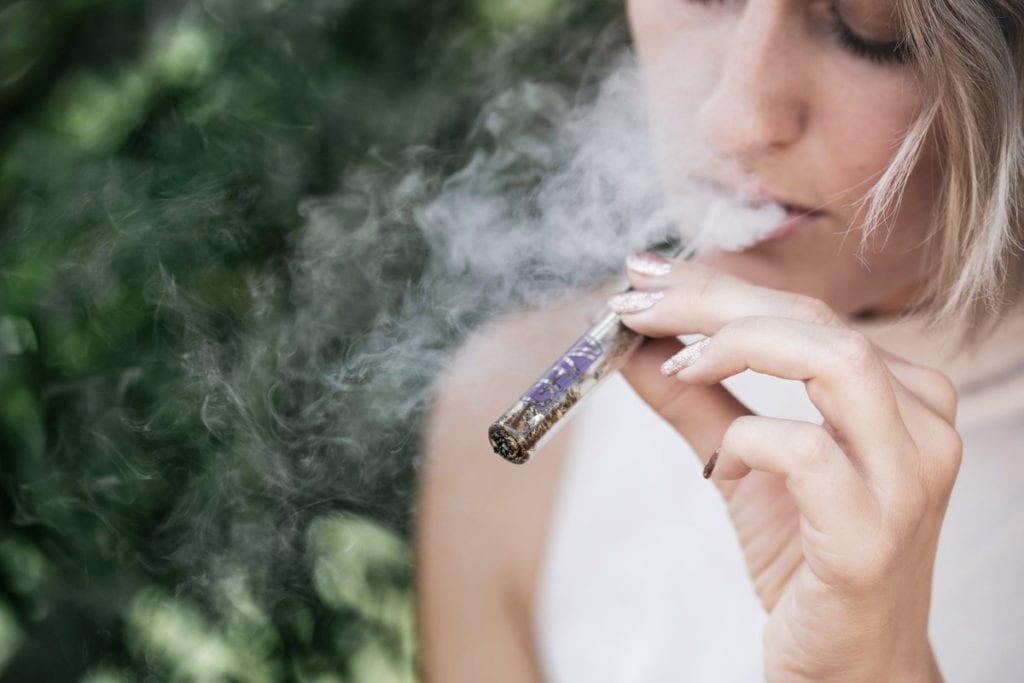 Young woman vaping marijuana.