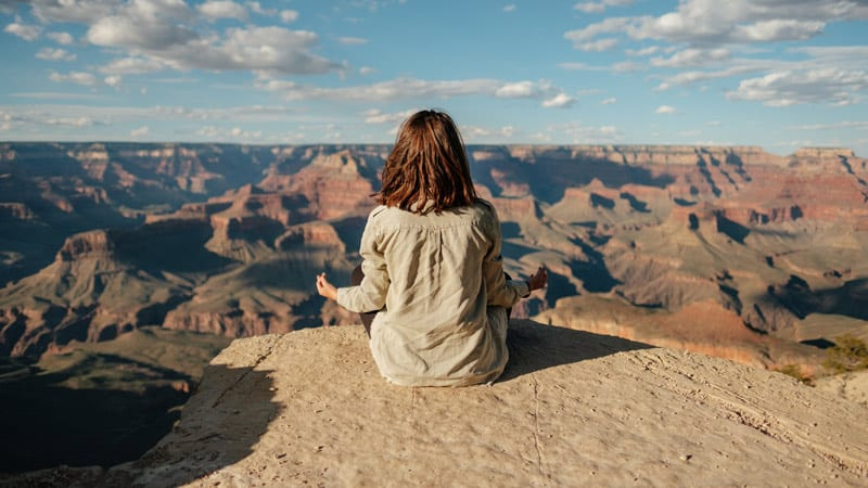 young woman meditating at Grand Canyon