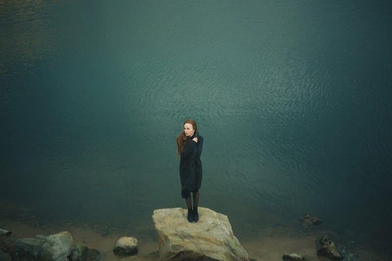 woman standing alone next to lake