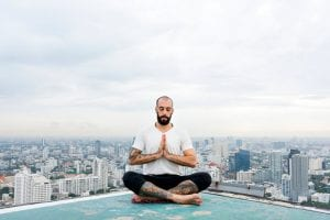 man doing rooftop meditation