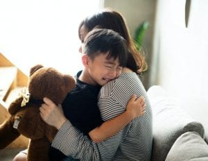 mother hugging crying child