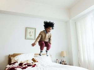 black child jumping on bed