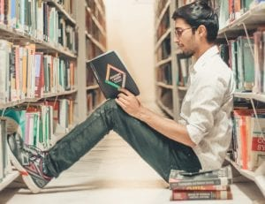 young adult reading in library