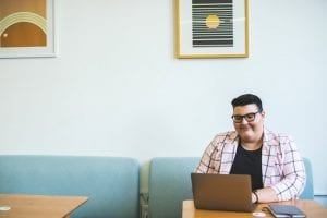 happy person using laptop on cushioned bench