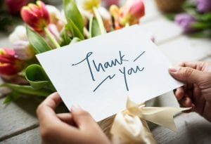 thank you note with flowers in background