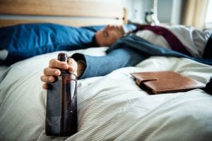 drunk businessman passed out on bed