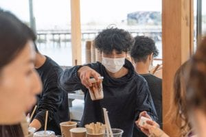 person in coffee shop wearing mask with to go cup